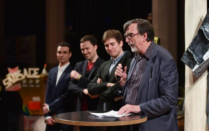A man talking to the audience. Further three men stand behind him