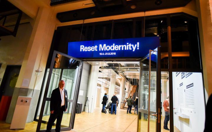 Leuchtreklame oberhalb einer Tür mit den Worten »Reset Modernity!«