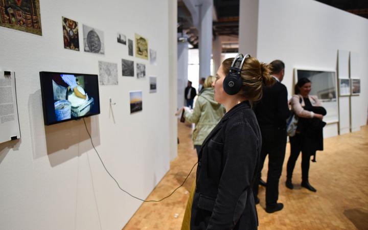 Eine Frau steht mit Kopfhörern vor einem kleinen Bildschirm