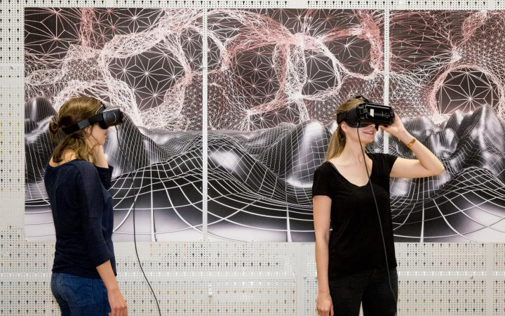 Two women look through VR glasses