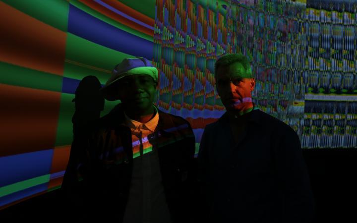 Zwei Männer stehen in einem dunklen Raum vor einem Screen mit bunten Farben.