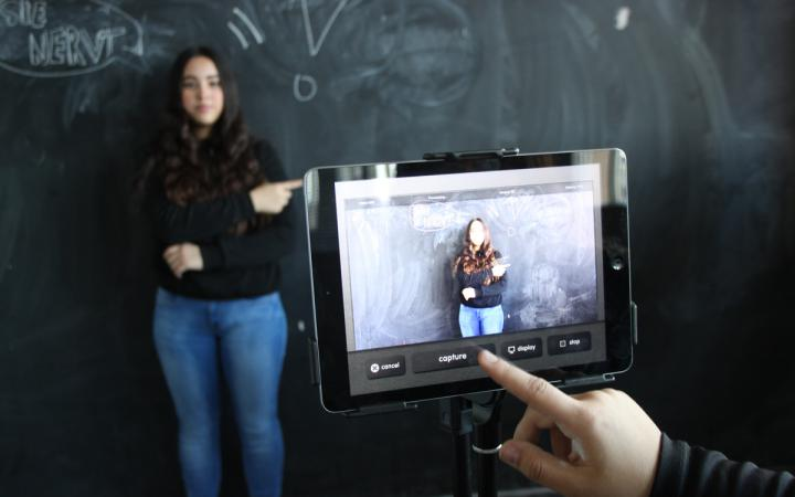 A girl standing in front of a board is being photographed with a tablet.