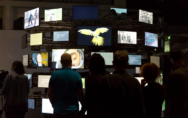 The picture shows visitors in front of a circularly arranged variety of differently screened screens.