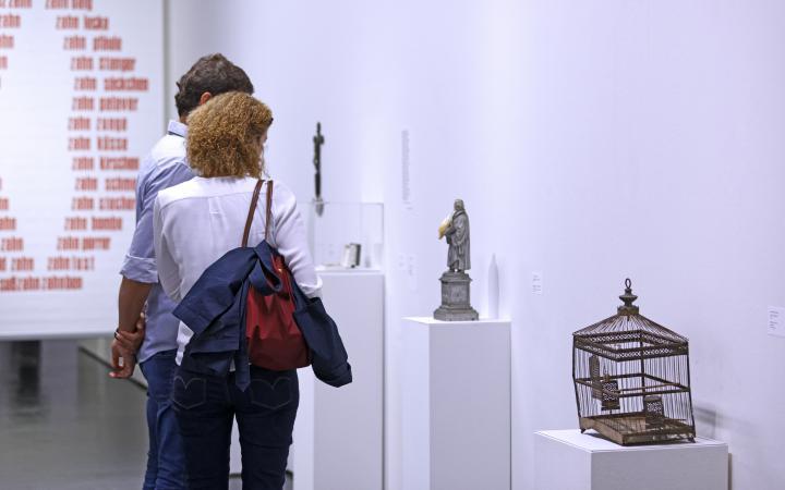 The photo shows visitors in front of artworks by Konrad Balder Schäuffelen