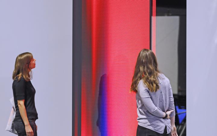 Besucherinnen vor einer 3,5 Meter hohen, rötlich leuchtenden »kosmischen«Leuchtskulptur.