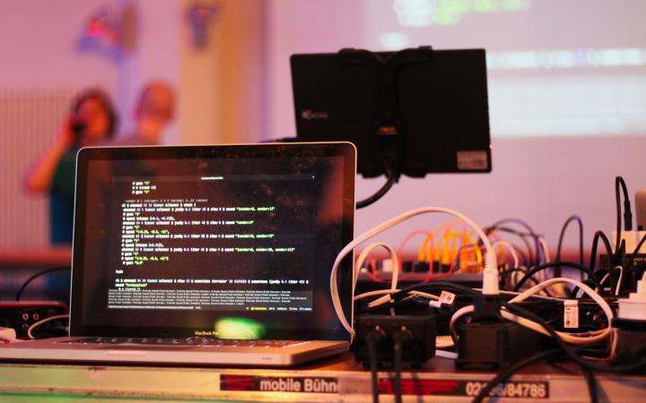 Auf einem Laptop ist Code zu sehen. Daneben liegen diverse Kabel.