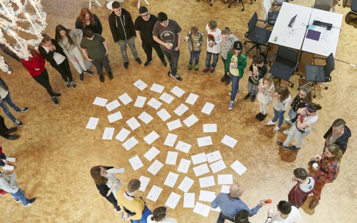 Einer Gruppe von jungen Menschen stehen im Ausstellungsraum um eine Ansammlung von Zeichnungen herum.