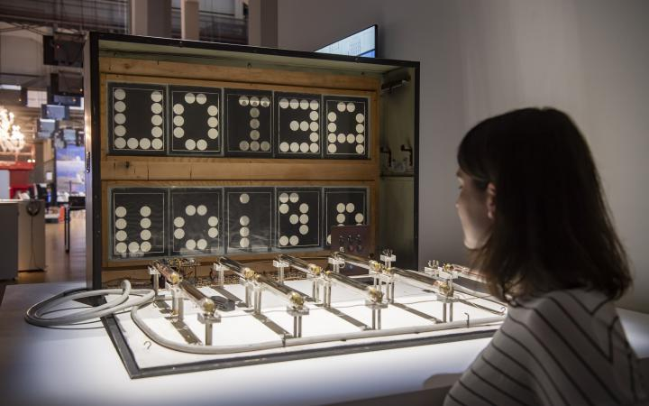 A woman stands in front of an installation consisting of several interconnected parallel bars and a box displaying letters.