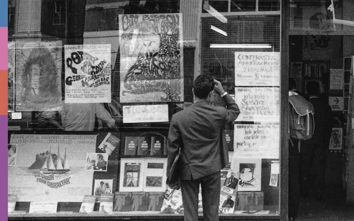 A man is standing in front of the window of the Better Books bookstore.