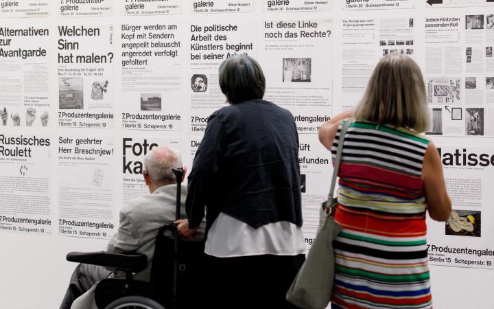 Das Bild zeigt drei Besucher vor Plakaten mit Typografie
