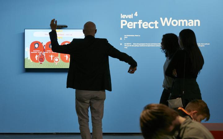 Vor einer blauen Wand, an der ein Bildschirm befestigt ist, steht ein Besucher mit erhobenen Armen. Weitere Zuschauen stehen betrachtend daneben.