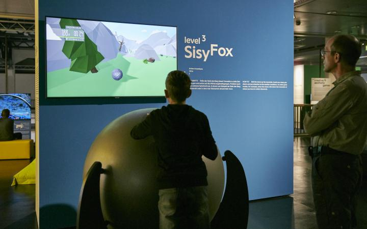 A young visitor in front of a game console consisting of a large ball on a rack. Behind a screen on a blue wall. Another visitor is standing next to it.