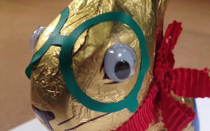 A golden chocolate Easter bunny looks into the camera with its wobbly eyes glued on. Beside the eyes a green sticker similar to glasses is glued on the packaging of the Easter bunny.