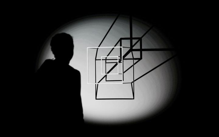 In einem Lichtkegel sieht man den Schatten einer Person und zwei weiße Vierecke, die ebenfalls einen schwarzen Schatten an die Wand werfen