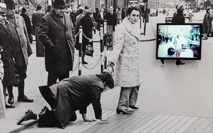 Ein schwarz-weiß Foto: Darauf ist Valie Export zu sehen, die Peter Weibel an der Leine durch eine Fußgängerzone führt.