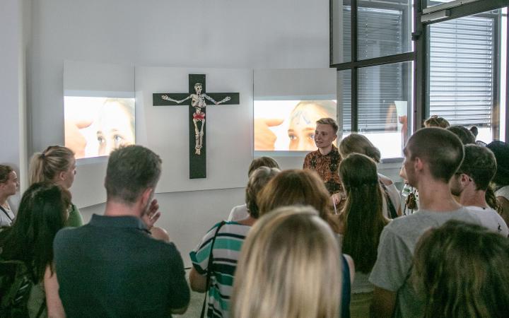 An der Wand hängt ein Kreuz mit einem Gerippe, als Triptychon werden daneben zwei Videos gezeigt. Vor dem Kunstwerk steht eine Menschenmenge.