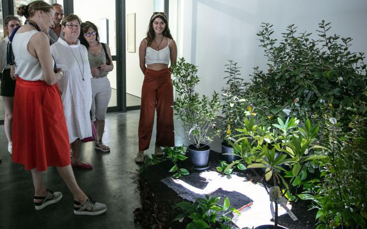 Eine junge Frau steht in einer Ausstellung neben vielen Grünpflanzen. Zwischen den Pflanzen sind die Umrisse eines Körpers zu sehen.