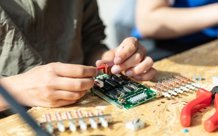 Zu sehen sind zwei Hände eines Schülers, die Bauteile zusammenlöten im Rahmen einer Veranstaltung der Kulturakademie.