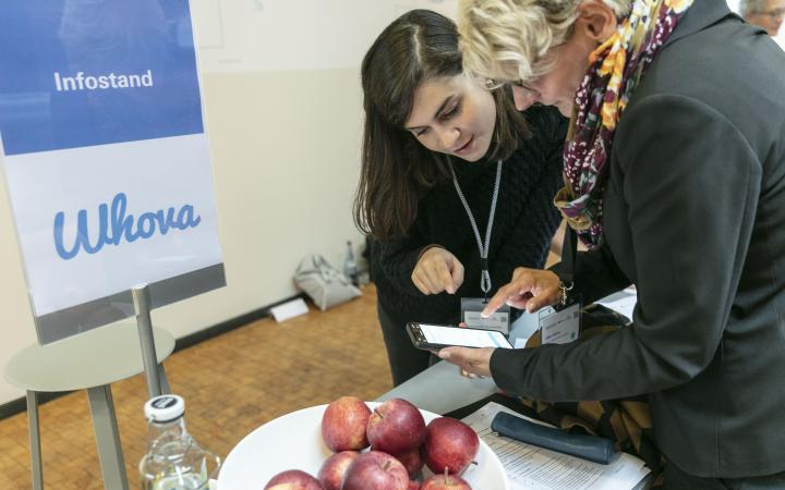 A person can be seen helping a participant with the conference app »Whova« at an event in the context of the forum »Digitale Welten BW«.