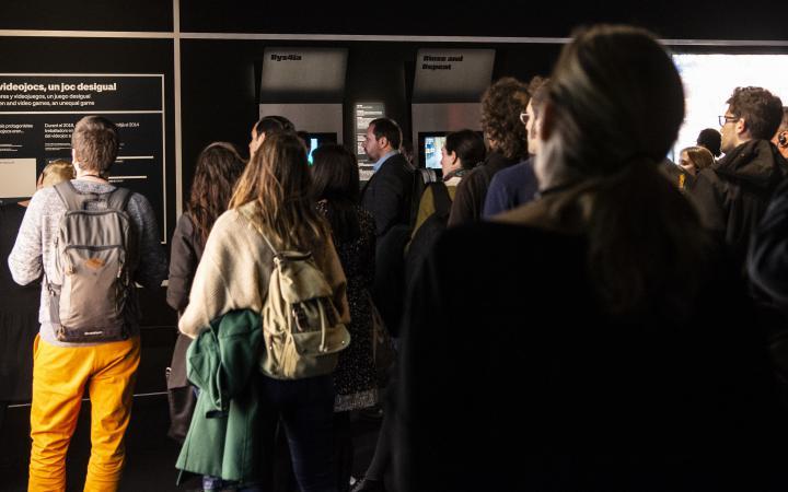 Eine Menschengruppe hat sich für eine Führung versammelt. Man sieht einen Mann ganz links mit einer hellgelben Hose, hinter ihm steht eine Frau mit einer dunkelgrünen Jacke über ihre Tasche gehangen. Sie hören aufmerksam dem Guide zu.