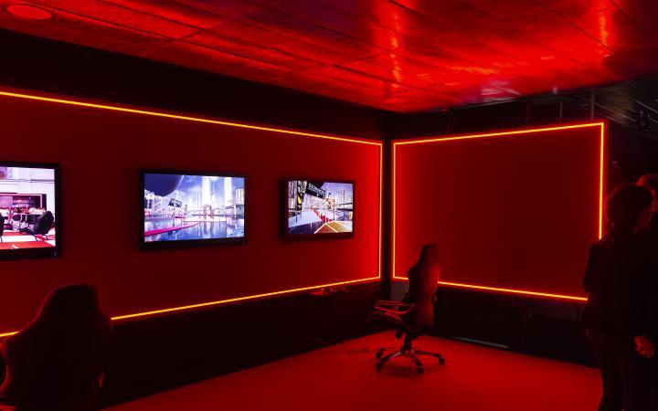 Das Foto zeigt einen rot erleuchteten Raum mit eleganten großen Bürostühlen. An der Wand sind drei Monitore angerichtet, davor stehen die Stühle.