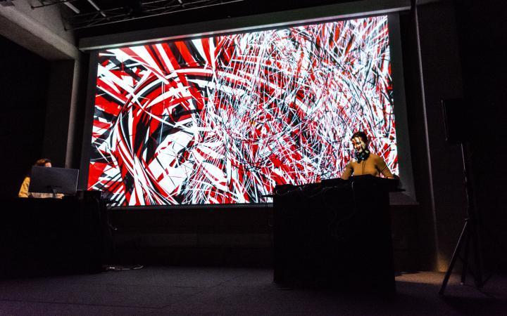 Zu sehen ist eine Visual-Sound-Performance. Zwei Frauen stehen an den unteren Ecken des großen Bildschirmes an ihren Soundcontrollern während im Hintergrund eine Farbstreifen aus rot schwarz und weiß eineinander verschmelzen.