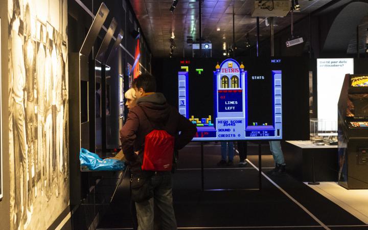 Zwei Menschen stehen vor einem Bildschirm im Ausstellungsraum »zkm_gameplay«.