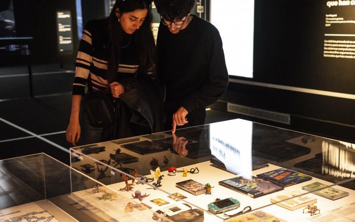 Zu sehen sind eine junge Frau und ein junger Mann, die sich über ein Schaufenster mit alten Video-Spiel-Figuren gebeut haben und diese bereden.