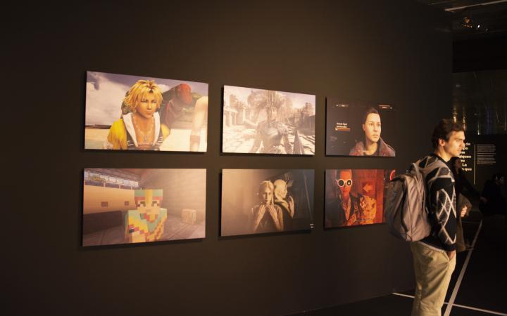 Auf der linken Seite des Bildes sind sechs Portraits von Charaktären aus verschiedenen Videospielen zu sehen. Auf der rechten Seite des Bildes steht ein Mann in grau und schwarz mit einem großen Rucksack.
