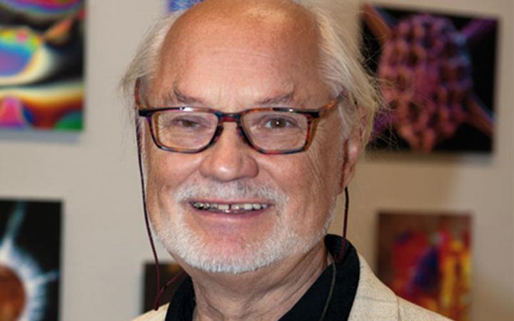 Der Künstler Manfred P. Kage vor seinen fotografischen Arbeiten.