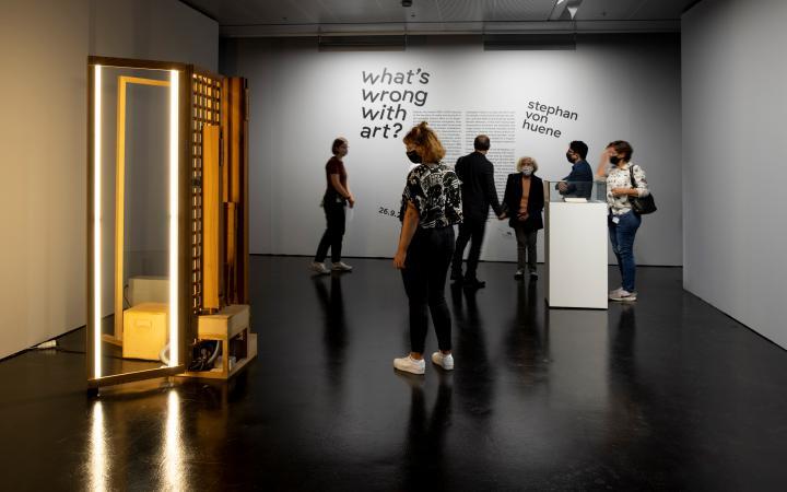 Einblick in die Ausstellung Stephan von Huene. Es sind 4 Menschen im Raum, links ist eine erleuchtete, rechteckige Standskulptur
