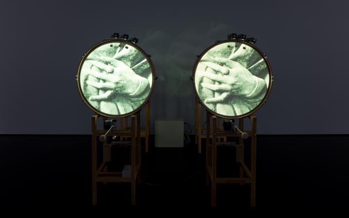 Zu sehen sind zwei stehende Trommeln, welche jeweils ein Bild von zwei ineinander gefalteten Händen auf der runden Fläche zeigen.