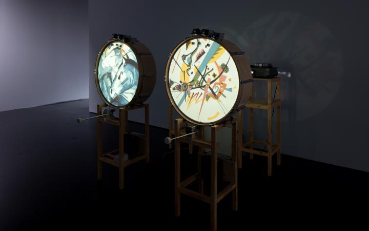 Zu sehen sind zwei stehende Trommeln, welche jeweils ein Bild von verschiedenen Formen auf der runden Fläche zeigen. Auf der linken Trommel ist ein Pferdekopf aus den Formen erkennbar.