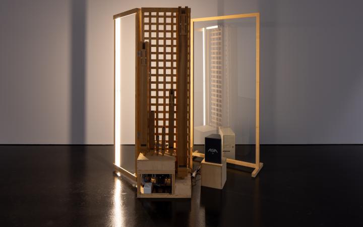 Zu sehen sind zwei Installationen aus Holz, welche zwei Türrahmen ähneln. In einem der Rahmen ist eine Glasscheibe. In dem anderen erkennt man ein Kairomuster aus Holzscheiten.