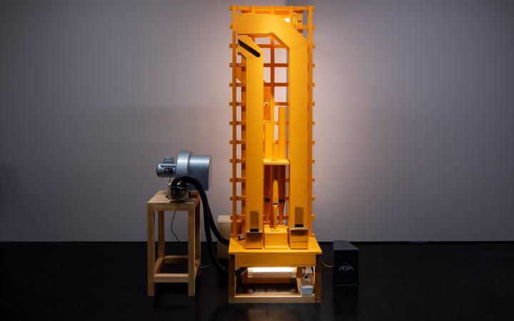 Zu sehen ist eine rechteckige, maschinenartige Installation, welche auf einem Hocker steht. Links neben der Installation steht ebenfalls ein kleiner Hocker, auf welchem ein Objekt liegt.