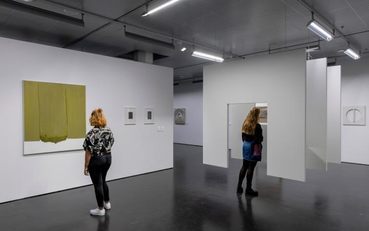 Two women in the exhibition room. On the left a woman is looking at a monochrome painting on the wall. In the middle, a woman is standing in front of a hanging construction consisting of three successive surfaces, with a passageway in between.
