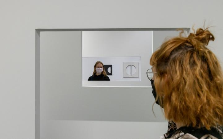 Two women in close-up. They stand opposite each other and look at each other through a hanging construction.