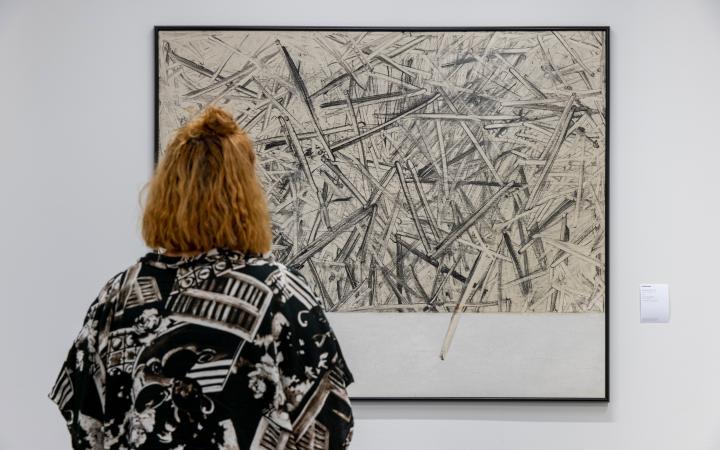 Eine Frau betrachtet ein an die Wand gehängtes Bild auf dem scharfe dicke Striche chaotisch aufeinander gemalt sind.