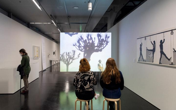 Three young women in the exhibition space. Two sit on stools in front of a film screen on which bare trees can be seen. An abstract drawing hangs on the wall to the right. On the left wall are boxes into which the third woman looks.