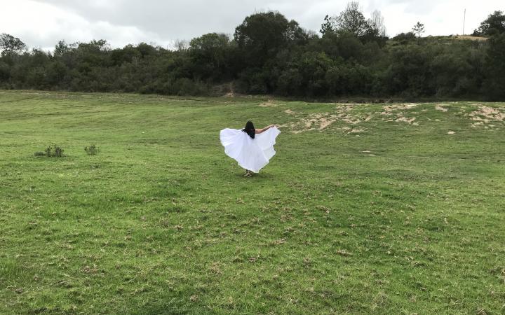 Eine Frau läuft in einem wehenden weißen Kleid über eine grüne Wiese vor einem Stück Wald.
