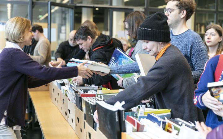 Viele Menschen bei einem Bücherflohmarkt.
