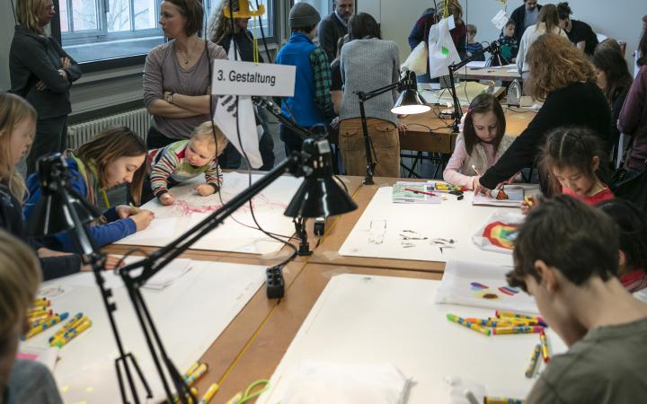 Many children paint at the table during a workshop.