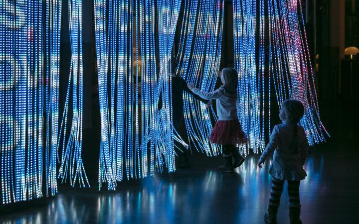 Zwei Kinder vor einem leuchtenden Vorhang am ZKM.