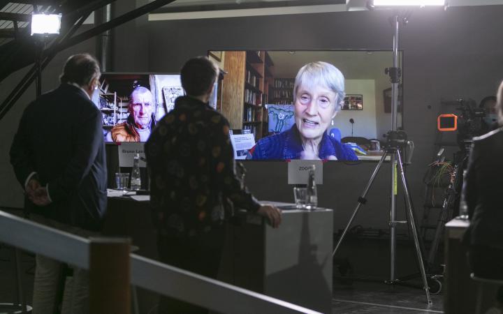 Donna Haraway ist auf einem großen Bildschirm zu sehen. Auf einem weiteren großen Bildschirm ist Bruno Latour zu sehen.