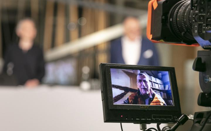 Im Vordergrund ist ein Video-Kamera-Display mit Bruno Latour drauf zu sehen. Hinter dem Display sind eine Frau und Peter Weibel verschwommen zu erkennen.