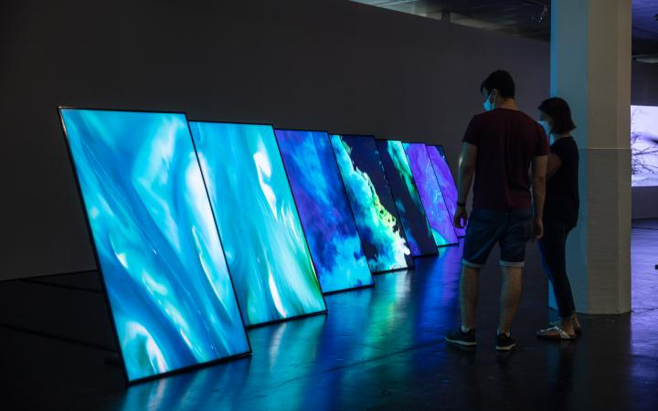 There are seven large flat screens on edge. The screens show aerial photographs of the sea.