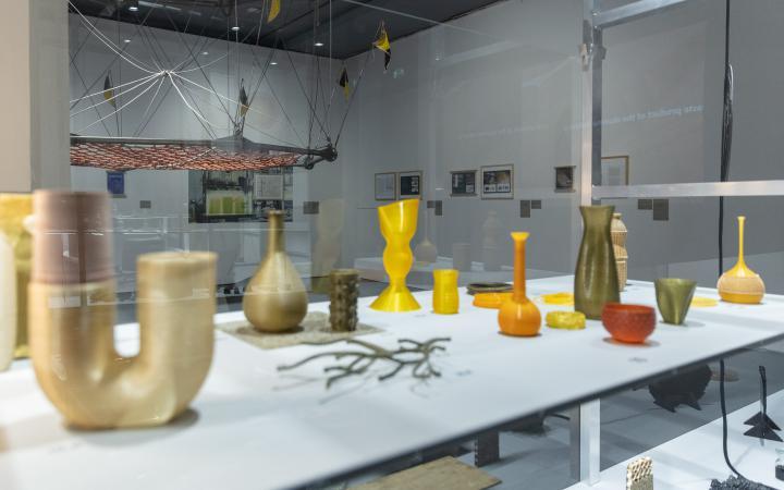 Zu sehen sind mehrere Vasen-förmige Objekte auf einem Tisch.
