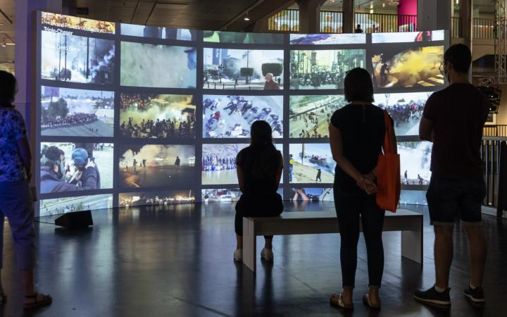 """The photo shows visitors sitting and standing in front of a large curved screen on the different windows with different images. It is the work """"Cloud Studies"""" by the artist collective Forensic Architecture."""