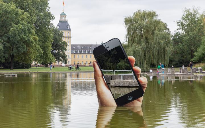 You can see the shore of a lake. A very large hand with a smartphone is sticking out of the lake. The display of the smartphone is a mirror in which the viewers can see themselves on the shore.