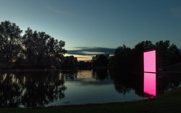 Zu sehen ist eine große quadratische Fläche, die im Dunkel der Nacht auf der Wasseroberfläche eines Sees zu stehen scheint. Auf der Fläche ist das Flackern eines Bildschirms zu erkennen.
